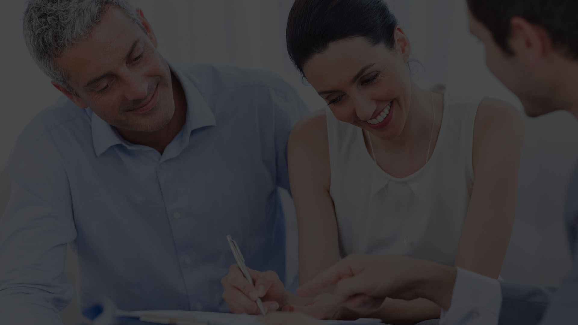 Couple smiling and signing paperwork